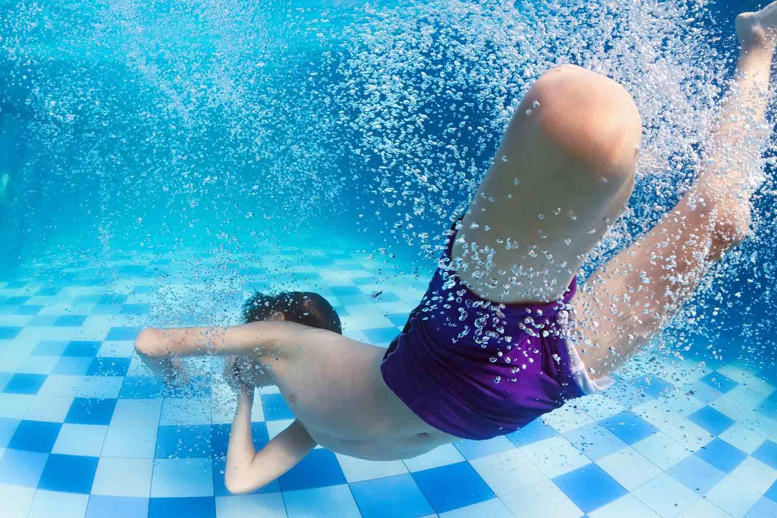 Gutt svømmer under vann