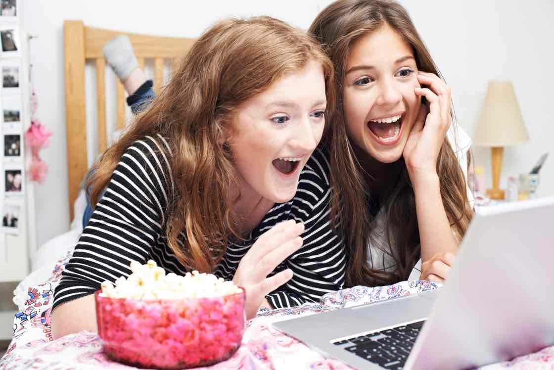 Two Teenage Girls Watching Movie On Laptop In Bedroom