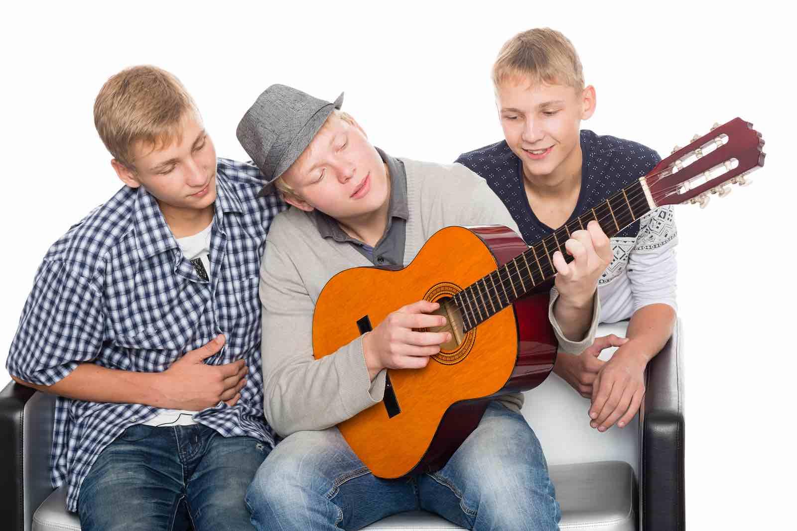 Tre gutter spiller gitar og synger