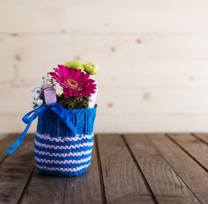 Small bouquet with gerbera and chrysanthemum in blue knitted vase on countrified wooden table